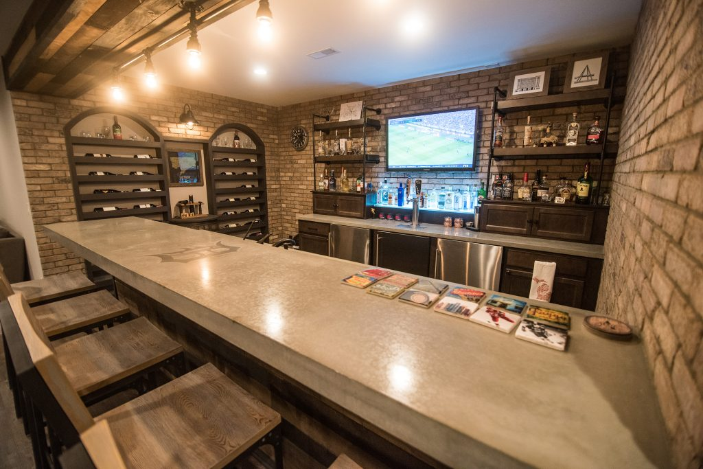 concrete countertops with an industrial style bar and brick walls