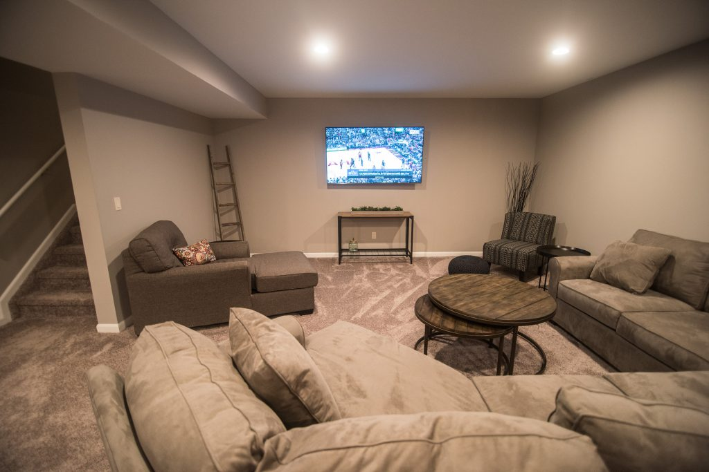 grey carpet with large couch and tv