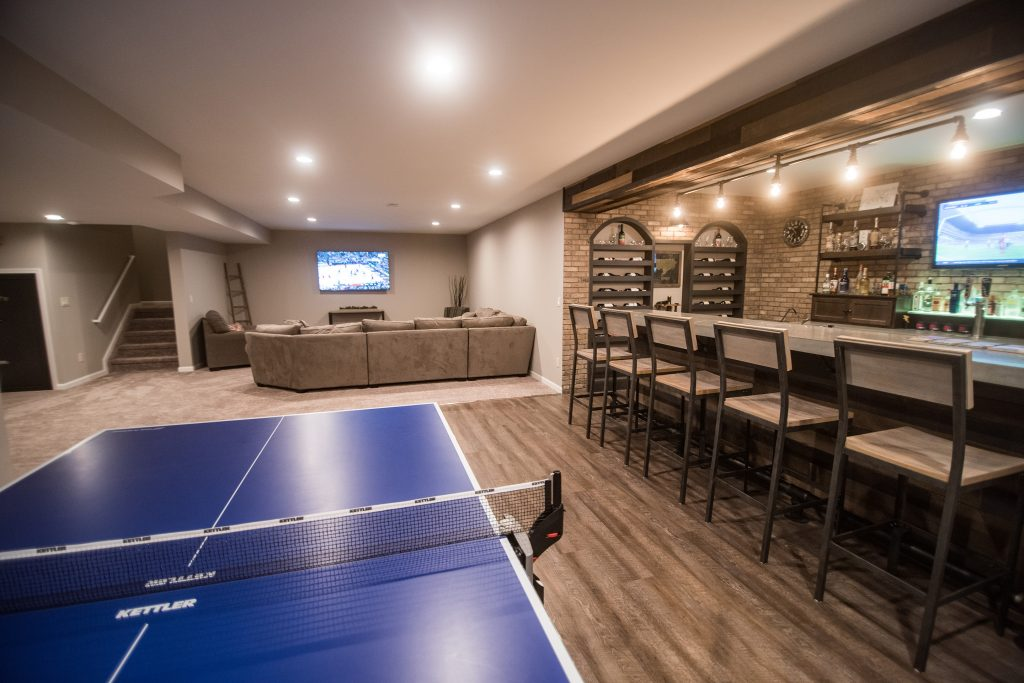 large finished basement with vinyl plank flooring and industrial bar