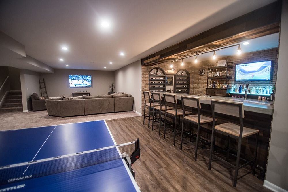 industrial basement design with bar and living room with vinyl plank