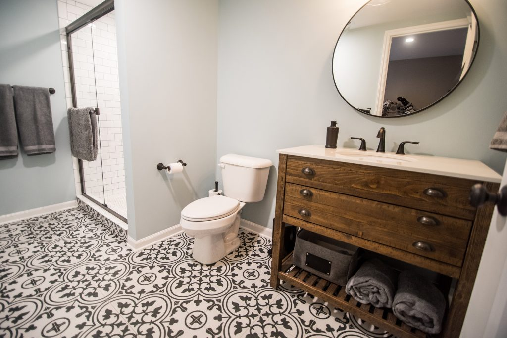 unique bathroom floor tile with black design and stained wood vanity