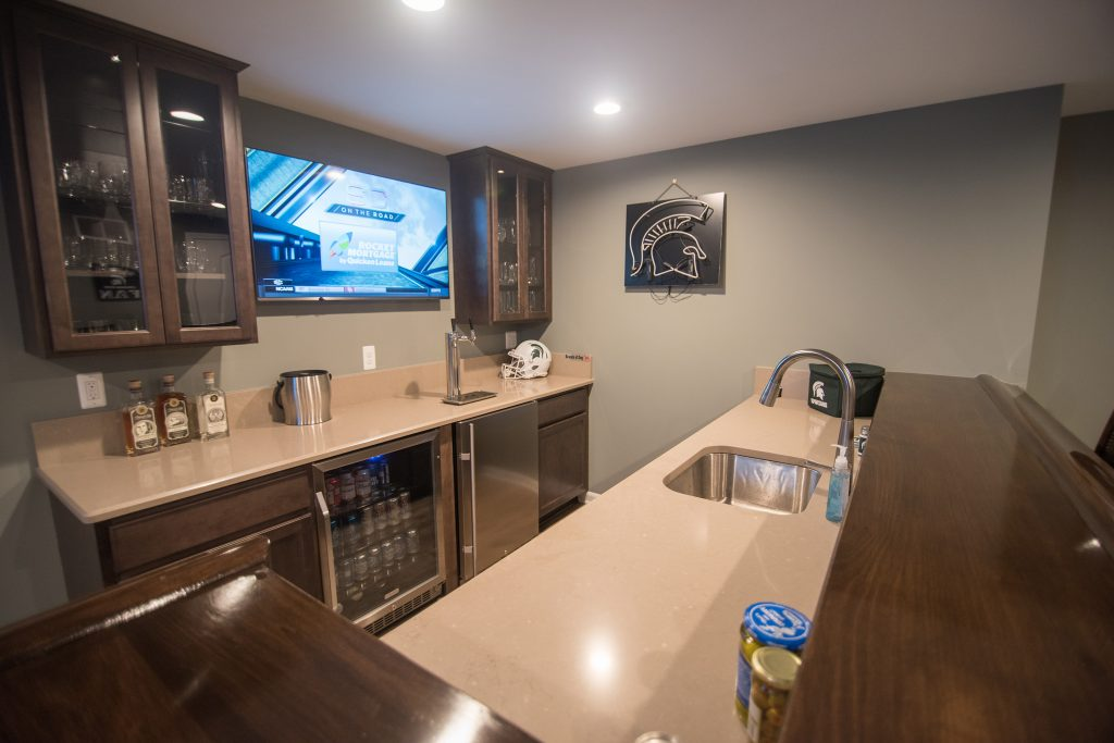 basement bar area with granite countertops and brown cabinets