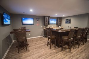 plenty of seating available in this basement bar with vinyl plank flooring