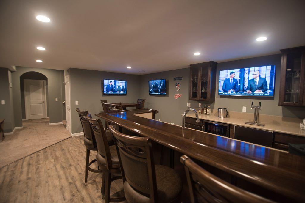 large sit at bar with seating and stained wood top