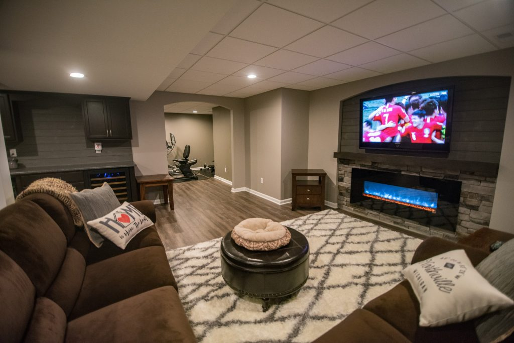 cozy basement living room with electric fireplace and sectional