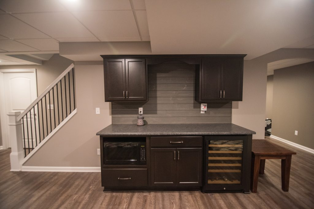 basement bar dark cabinets and shiplap backsplash