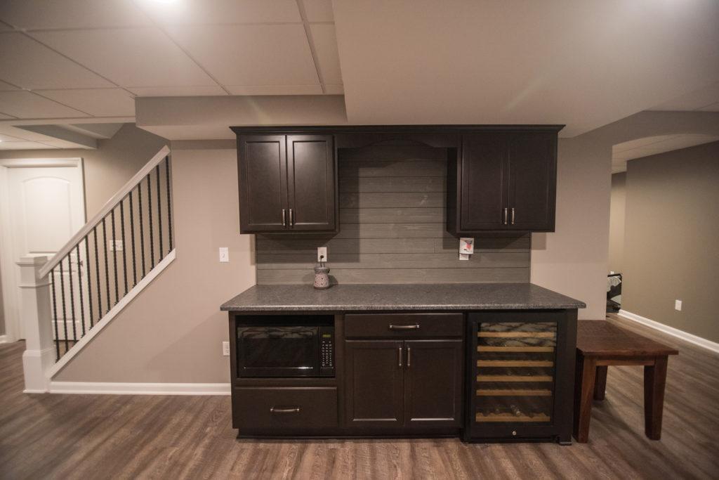 basement bar dark cabinets and shiplap backsplash