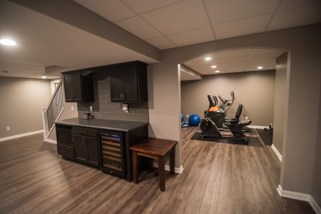 basement bar with adjacent fitness room with archway
