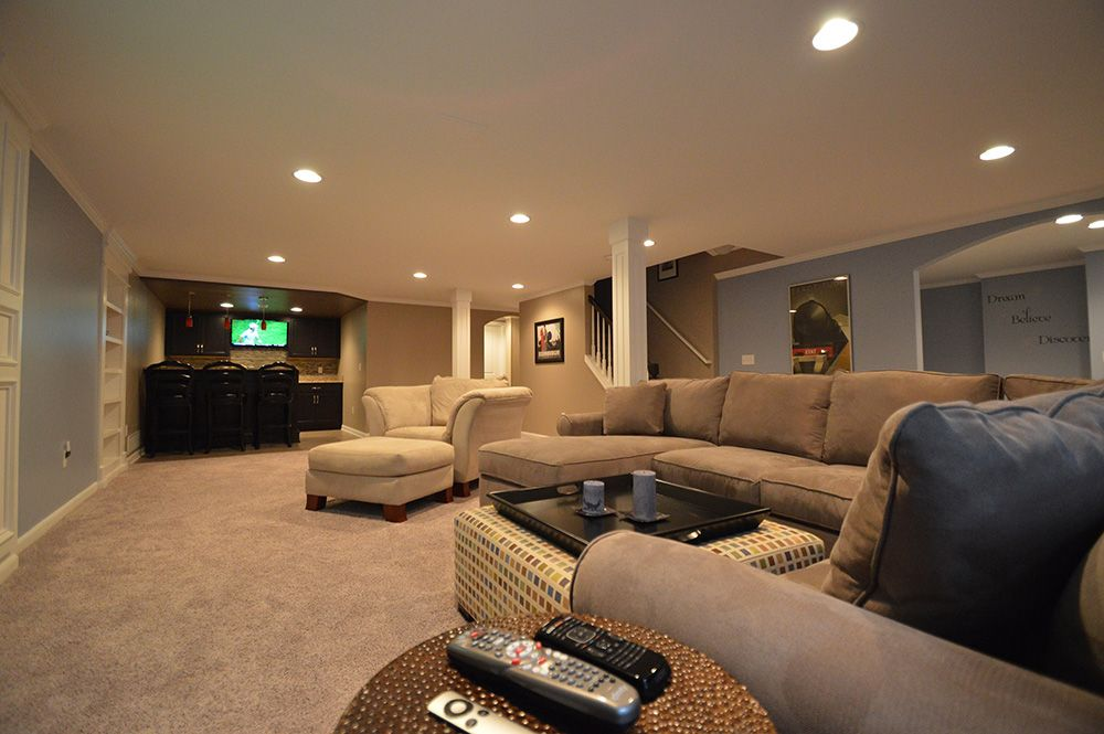 large open basement living room with brown and blue walls a living room sofa and a bar in the end