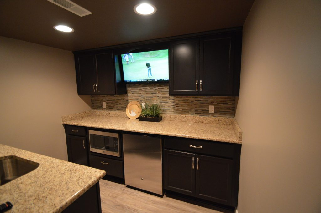 basement bar with dark cabinetry and granite countertops