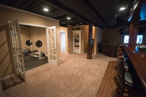 basement with fitness room behind french doors with carpet