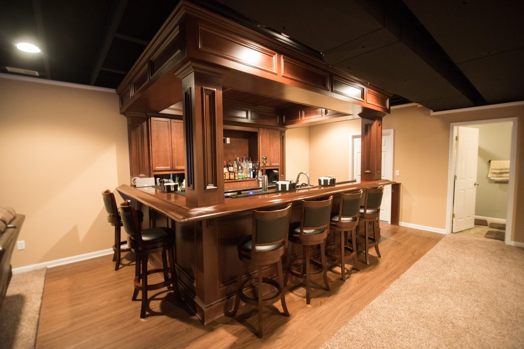 decorative pub style bar with wood details and soffet above bar