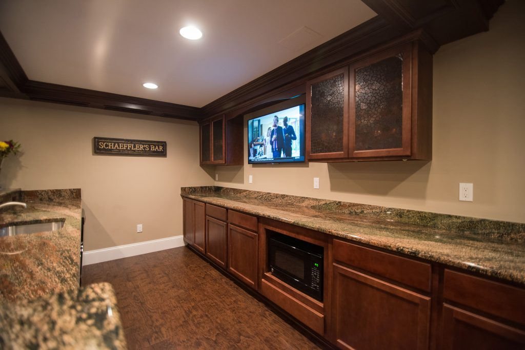 traditional style pub bar in basement with vinyl plank flooring