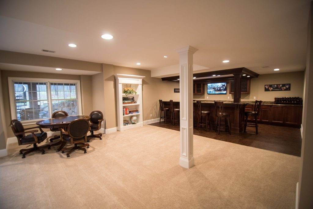 spacious basement living room with carpet and post wrap