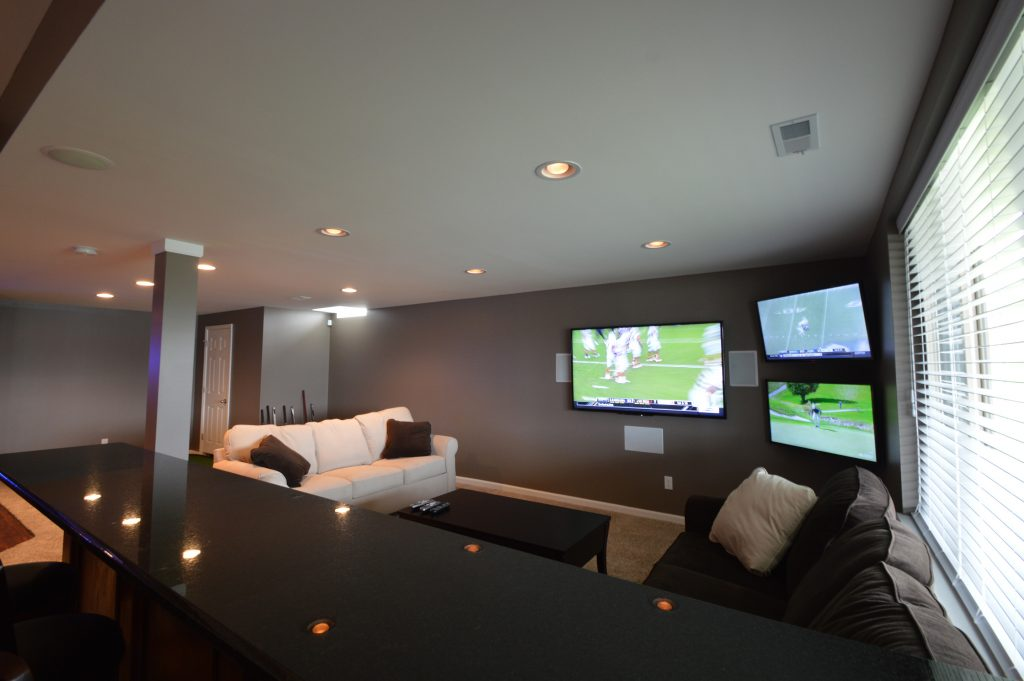 basement living room with granite seating area behind couch