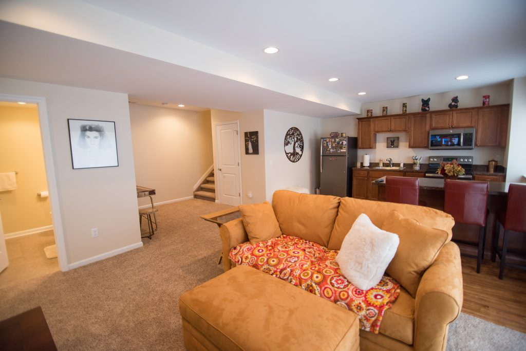 open concept basement with carpeting and kitchen