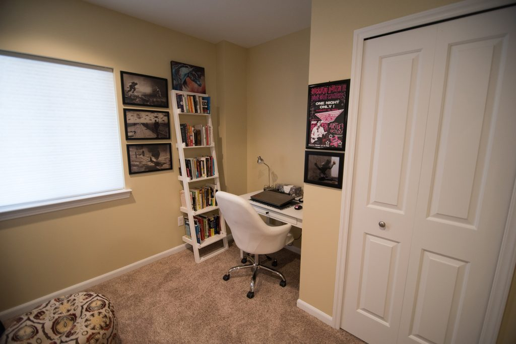 small home office in basement with desk and carpet