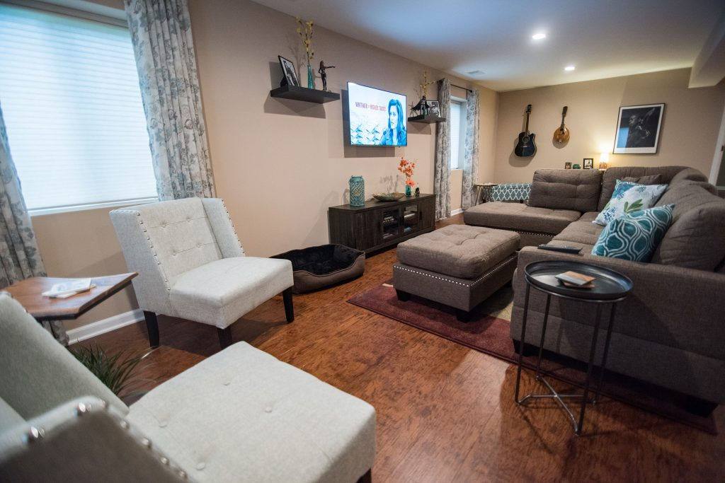basement living room area with sectional for entertaining