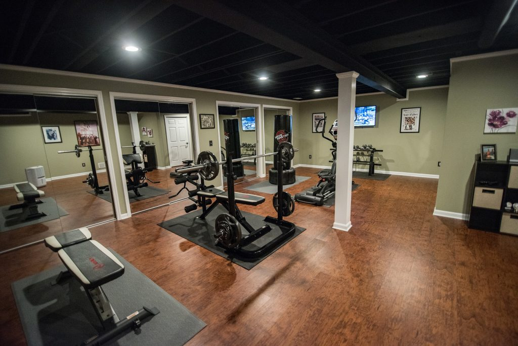 basement fitness room with vinyl plank flooring