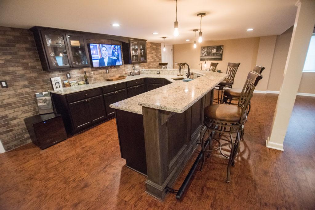 basement bar with dark cabinetry and granite countertops