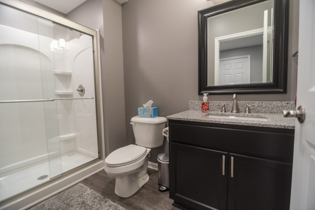 finished bathroom in basement with vinyl plank and shower