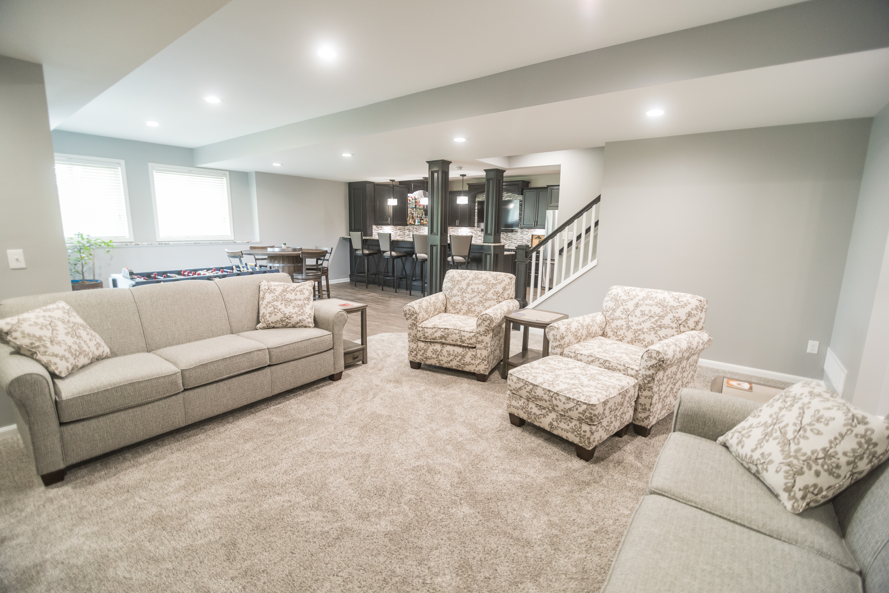walkout basement with bright lighting and grey walls and carpet