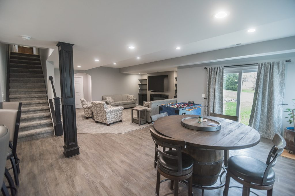 finished basement with bar and game table with rustic design