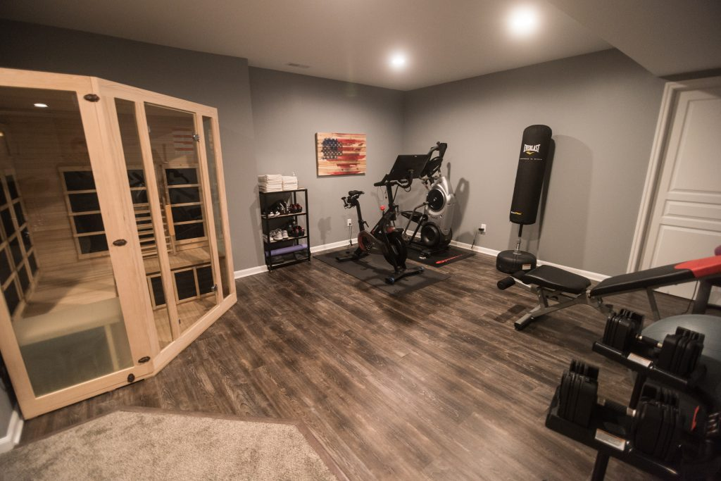 fitness space in basement with vinyl plank flooring and sauna