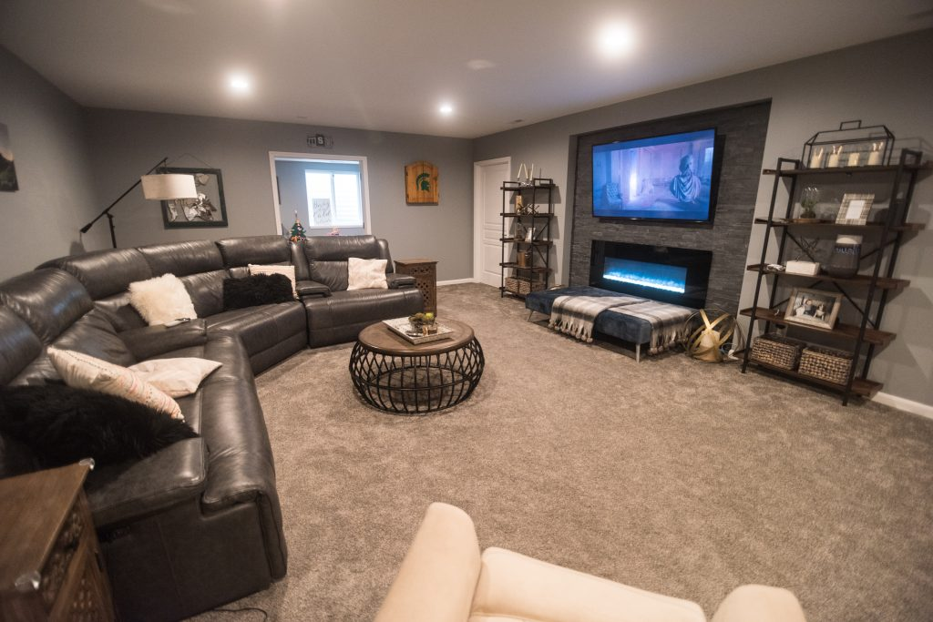 open concept finished basement with stone niche with tv and closed off playroom for kids