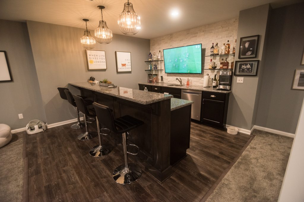 A bright inviting home bar with stone work on the walls and farmhouse style decorations