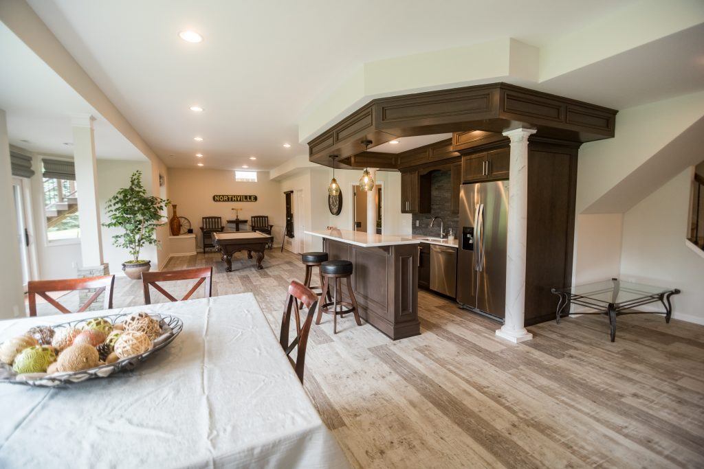 open floorplan basement with bar in the middle with soffit and dark stain