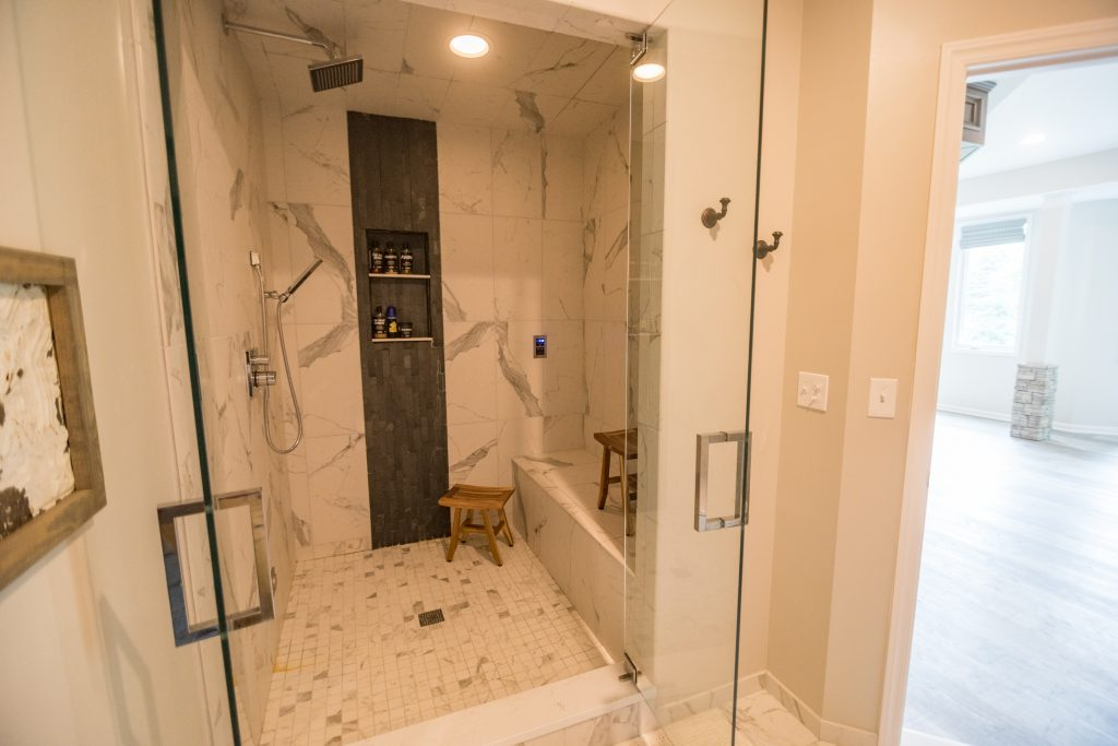 tile steam shower in basement with dark tile accent
