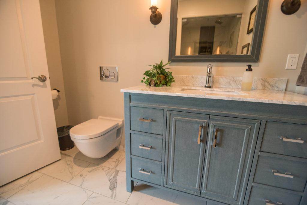 blue vanity in tiled bathroom for a pop of color