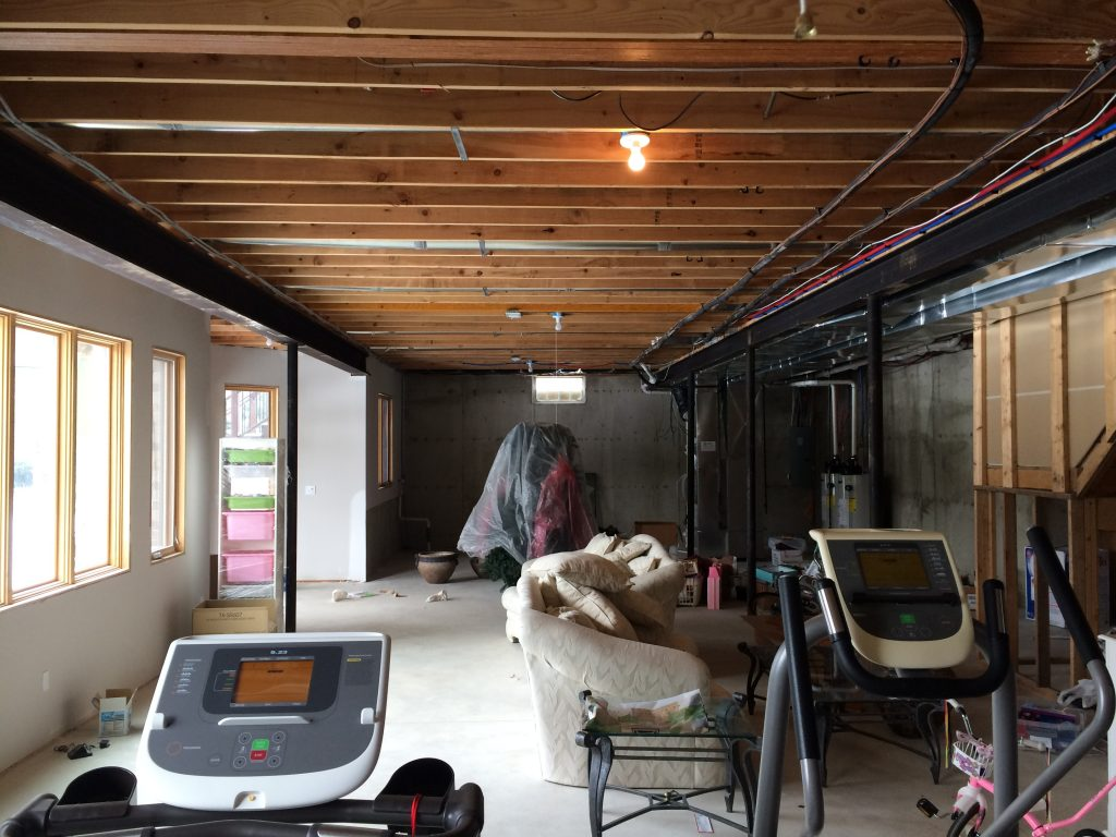 unfinsihed basement with exposed ceiling joists and concrete flooring