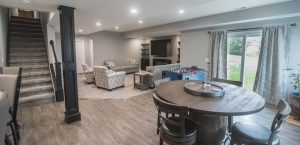 finished walkout basement with light brown vinyl plank flooring and modern design
