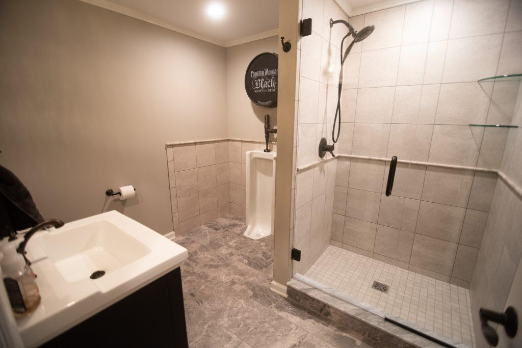 urinal in finished basement with ceramic tile shower