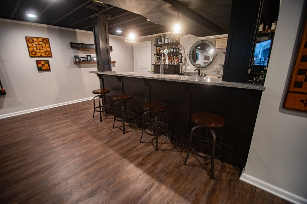 basement bar with dark cabinets and granite countertops
