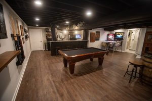 pool table in basement with dark brown vinyl plank flooring and painted ceiling