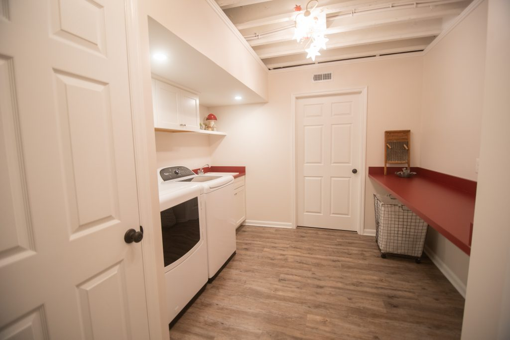 finished basement laundry with painted white ceiling and storage red countertops