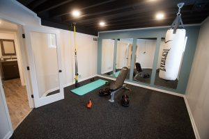 finished home gym in basement with fitness space and mirror panels