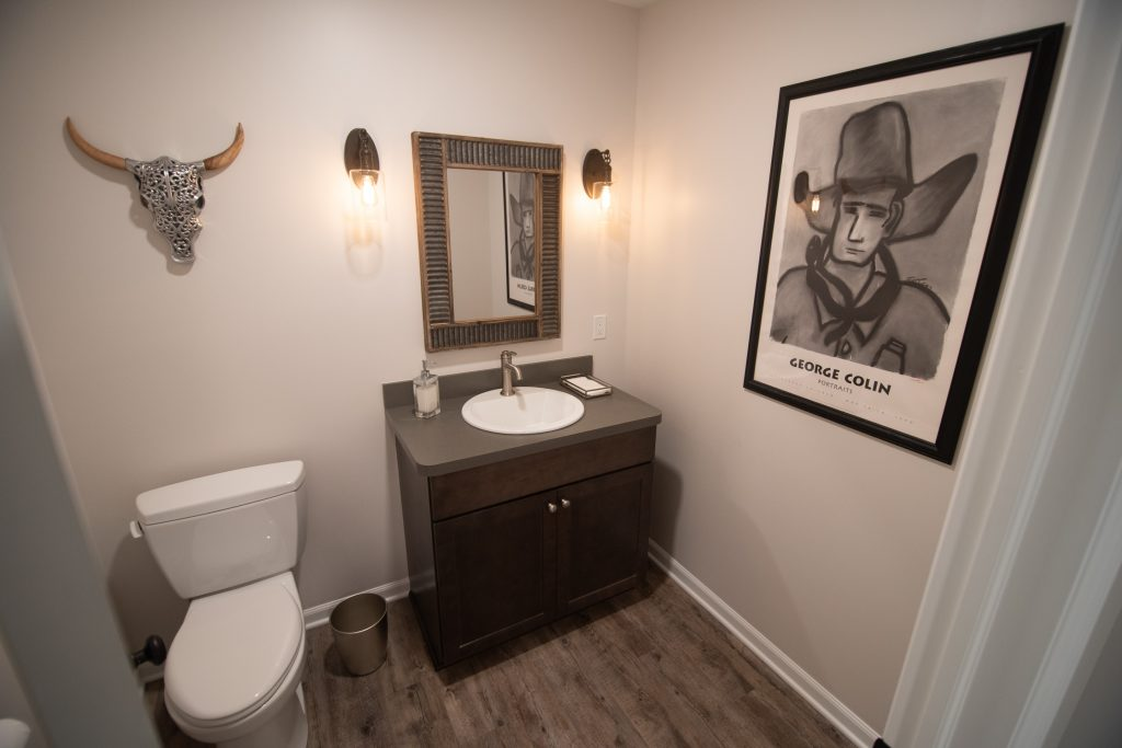 finished basement bathroom with brown vanity and light brown vinyl plank flooring and sconce lighting