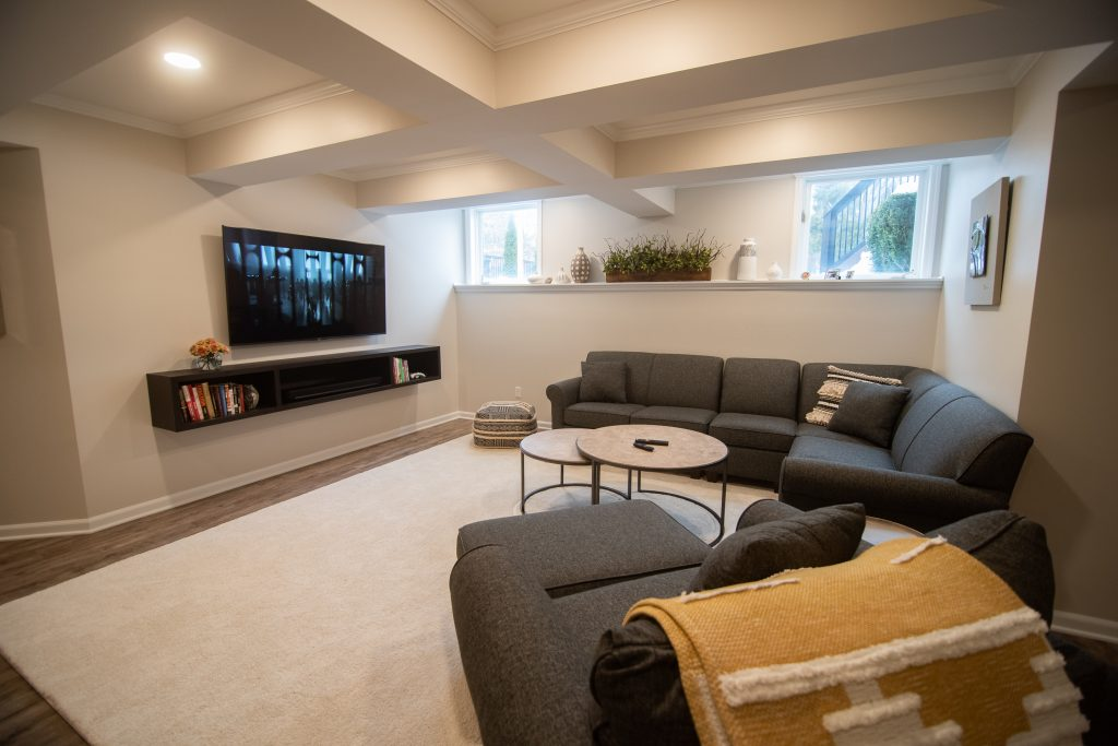 finished basement living room with media center and ceiling detail daylight wall