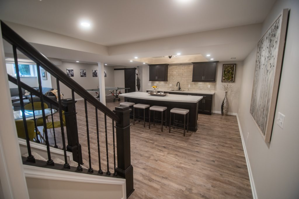 open rail basement staircase with brown vinyl plank flooring and bar