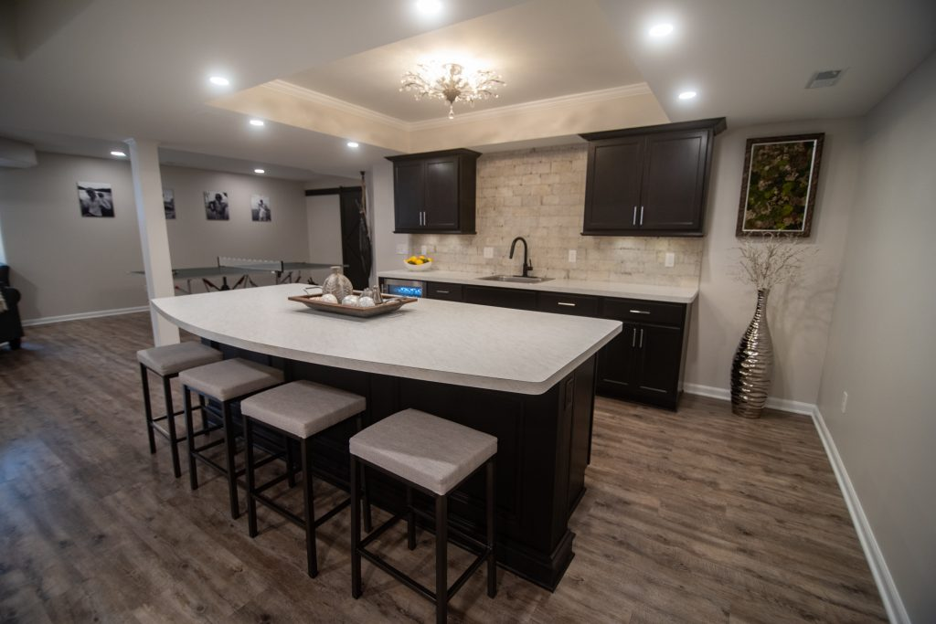 basement bar with white marble laminate countertops and dark brown cabinetry