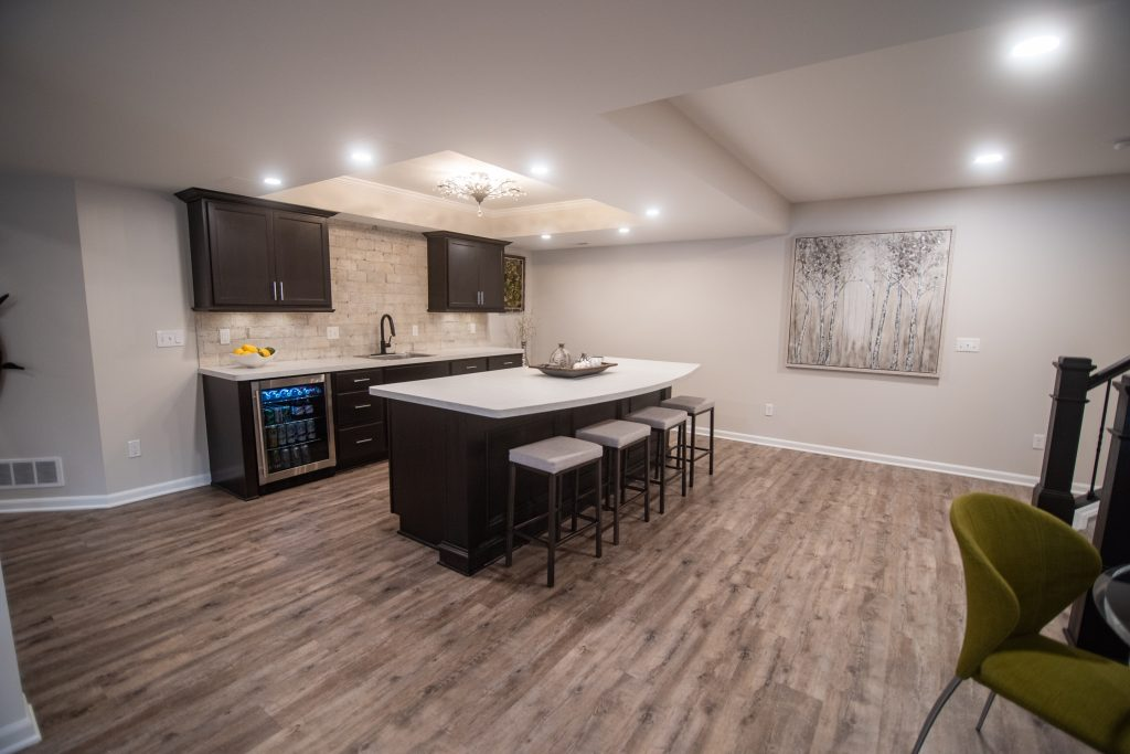 basement bar area with white laminate countertops brown cabinets and light brown vinyl plank flooring