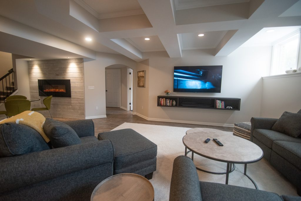 entertainment living room space in basement with ceiling detail and floating console table