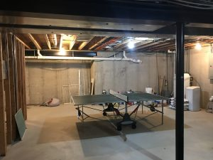 Ping pong table on cement in unfinished basement