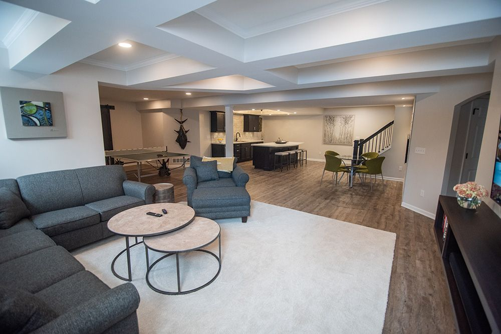 bright open concept living room design finished basement with vinyl plank flooring