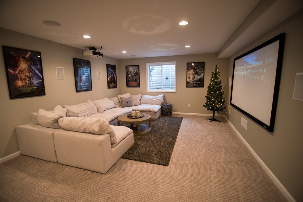 basement with home theater set up projection screen and movie posters