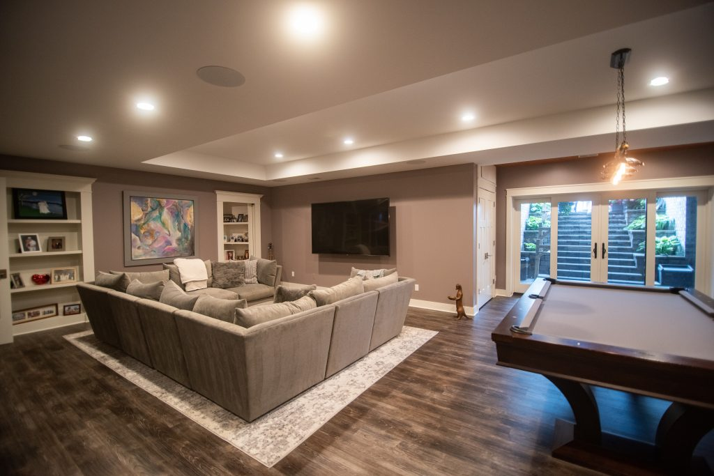 tv area in basement with wall mounted tv and sectional